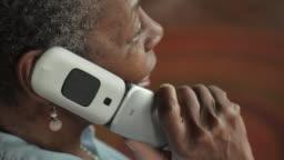 Happy friendly senior black woman opening a flip phone and talking - OTS