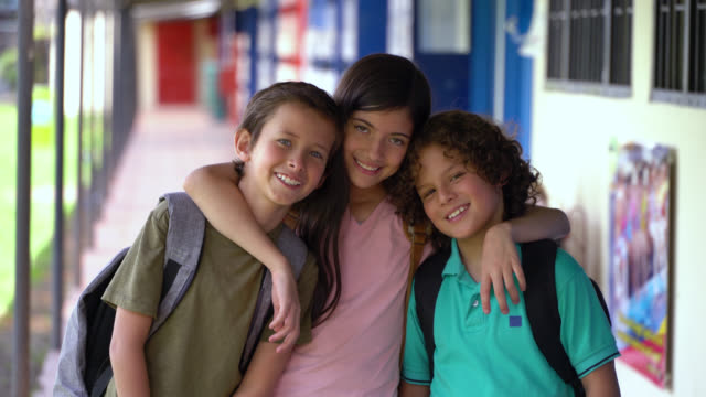 happy friends at school hugging while facing camera smiling - bambini maschi video stock e b–roll