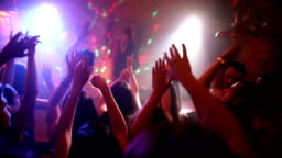 Happy friends dancing in disco with arms raised with beautiful female DJ on stage