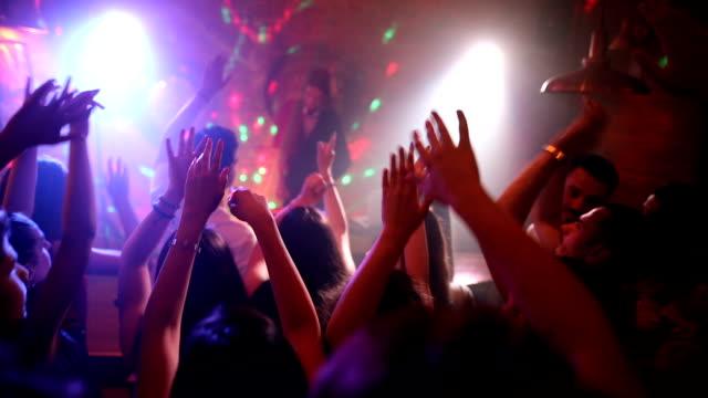 vidéos et rushes de amis heureux dansant dans le disco avec des bras soulevés avec le beau dj féminin sur l'étape - concert