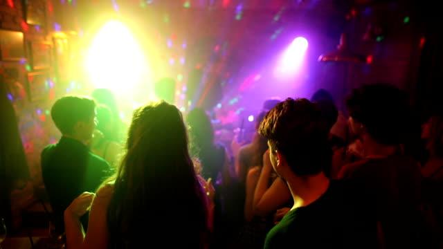 vídeos de stock, filmes e b-roll de amigos felizes que dançam no disco com os braços levantados com o dj fêmea bonito no estágio - meninos adolescentes