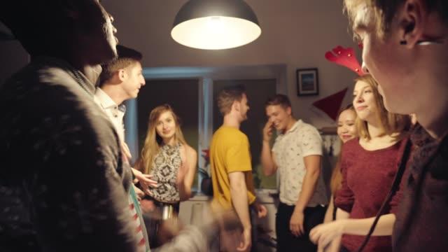 vídeos de stock, filmes e b-roll de amigos felizes dançando na sala iluminada na festa - male friendship