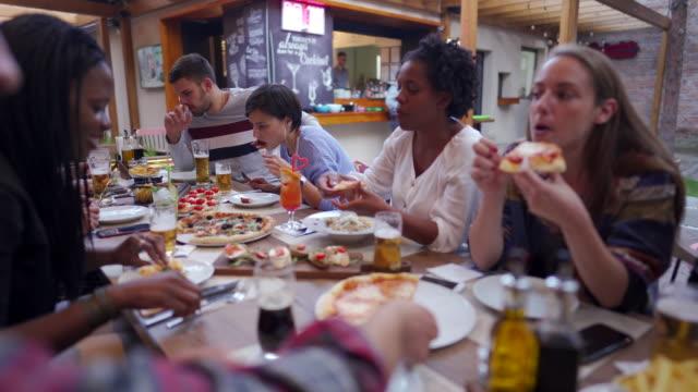 glada vänner äter och pratar på utomhuspizzeria - skvaller bildbanksvideor och videomaterial från bakom kulisserna