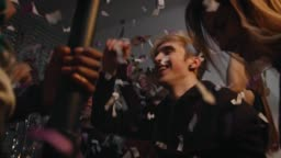 Happy friends enjoying with confetti in party