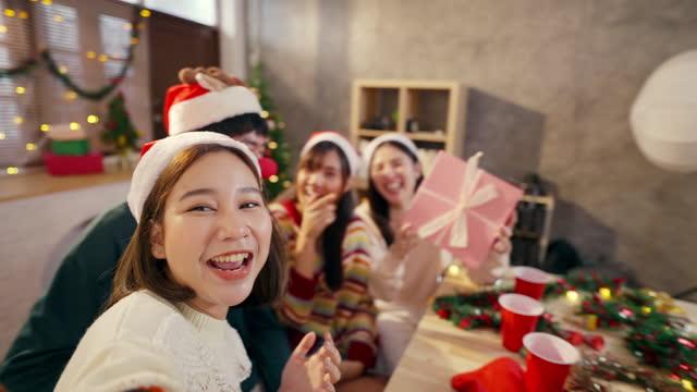 自宅で集まる間、スマートフォンを使用して幸せな友人グループが写真を撮ります - 自画像点の映像素材/bロール