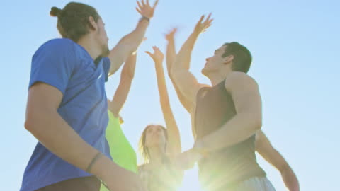 happy friends high-fiving in mid-air during sunset - five people stock videos & royalty-free footage