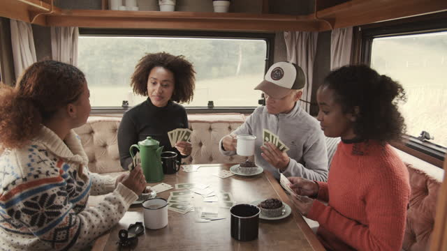 happy friends playing game in motor home - playing card stock videos & royalty-free footage
