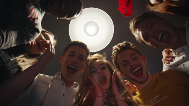happy friends shouting in illuminated room - pendant light stock videos & royalty-free footage