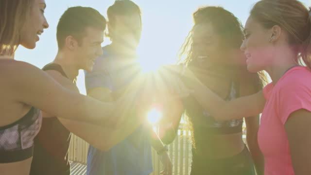 vídeos de stock e filmes b-roll de happy friends stacking hands on bridge against sky - stack