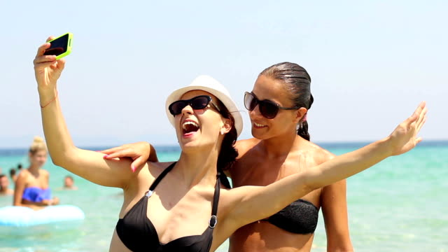 Happy friends taking a selfie at the beach in summer