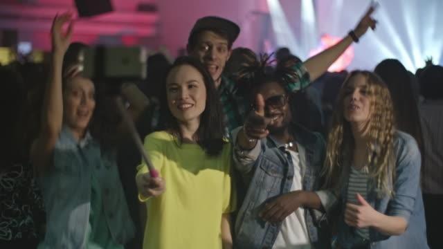 vídeos y material grabado en eventos de stock de happy friends taking selfies at concert - photographing