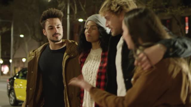 vídeos de stock, filmes e b-roll de amigos felizes falando enquanto cidade de travessia de rua - male friendship
