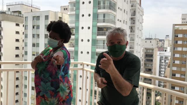 vídeos de stock, filmes e b-roll de amigos felizes usando máscara facial dançando na varanda do apartamento - sacada