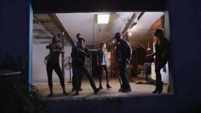 happy fun loving friends having dance party in open urban studio garage - dance studio stock videos and b-roll footage