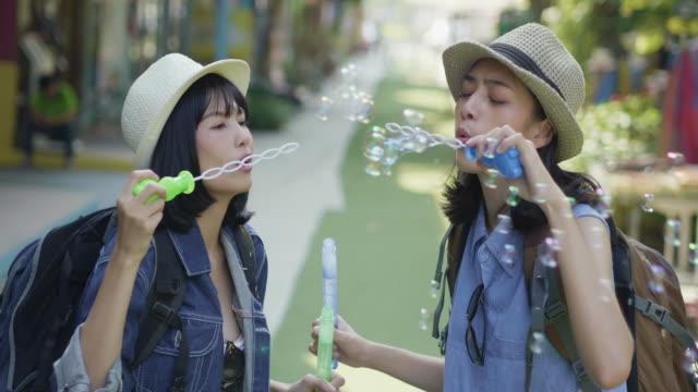Femmes de l'heureux couple drôle jouant ensemble soufflant des bulles de savon en vacances. Concept de LGBT. Femmes de l'heureux couple drôle jouant ensemble soufflant des bulles de savon en vacances. Concept de LGBT.