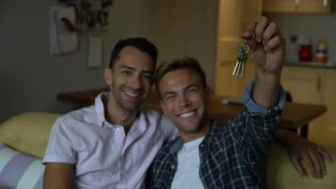 happy gay couple at home holding the keys to their new home - new stock videos & royalty-free footage