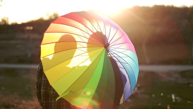 vídeos de stock e filmes b-roll de casal gay feliz por trás do guarda-chuva - chapéu