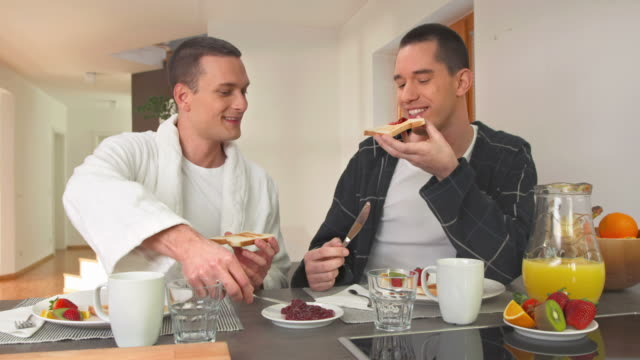 hd dolly: happy gay paar essen frühstück - freundschaftliche verbundenheit stock-videos und b-roll-filmmaterial