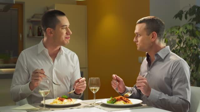 hd: felice coppia gay mangiare la cena - spaghetti video stock e b–roll
