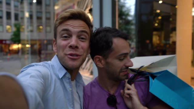 幸せなゲイのカップルが興奮している彼らのショッピングバッグで自分撮りを取って - 自画像点の映像素材/bロール