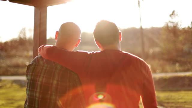 vídeos de stock, filmes e b-roll de homossexual feliz casal assistindo ao pôr-do-sol - homem homossexual