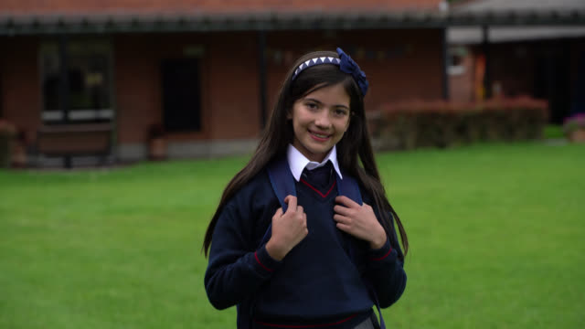happy girl at school looking at camera smiling while holding the straps of her backpack - education concepts - school uniform stock videos & royalty-free footage