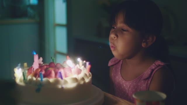 glückliches mädchen blasen kerzen auf einem geburtstagstorte - candlelight stock-videos und b-roll-filmmaterial