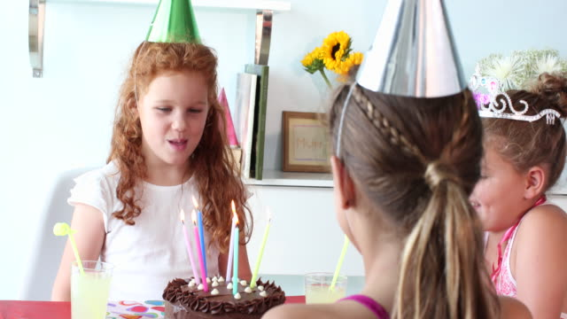 Happy girl blowing out candles on birthday cake at a party.