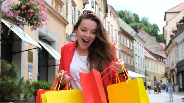 happy girl checking her shopping bags - shopaholic stock videos & royalty-free footage