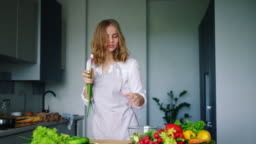 Happy girl dancing and singing in kitchen using cucumber as microphone