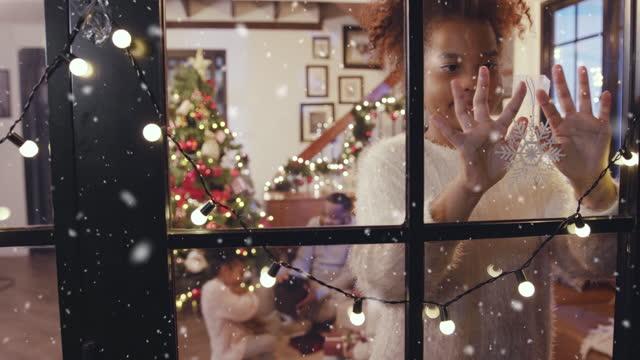 ragazza felice che decora fiocco di neve alla finestra mentre prima la neve cade, l'inverno e il concetto di scena natalizia - ornato video stock e b–roll