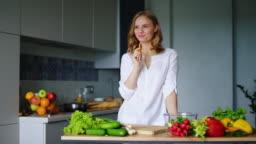 Happy girl eating carrot in kitchen. Healthy eating. Vegetarian food