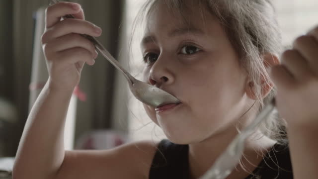 happy girl eating delicious food with spoon. - povertà video stock e b–roll