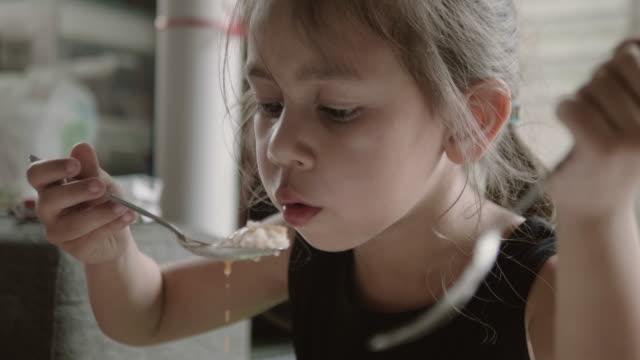 vidéos et rushes de fille heureuse, manger de la nourriture délicieuse avec la cuillère. - riz céréale