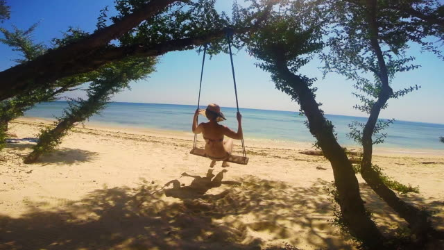 Happy girl enjoy vacations in the islands of Indonesia playing with swing in front of the beach with beautiful views.