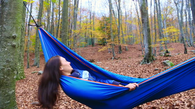stockvideo's en b-roll-footage met happy girl enjoying autumn season in a nice forest with colorful leafs during trip in the montseny mountain resting in a hammock swinging between the nature contemplating the beautiful trees in a unique place. - achterover leunen