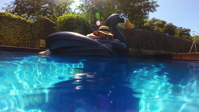 happy girl enjoying summer in swimming pool with big inflatable black swan sunbathing and relaxing in the sun during weekend. - inflatable stock videos & royalty-free footage