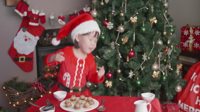 happy girl help preparing christmas pudding  in front of christmas tree at home - one baby girl only stock videos & royalty-free footage