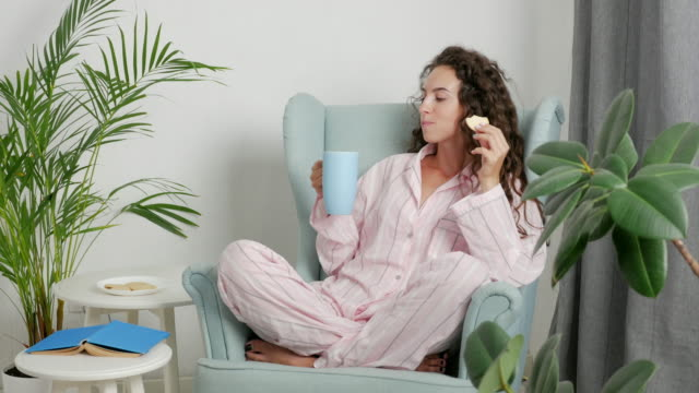 happy girl in pajamas drinking tea and eating cookies - biscuit stock videos & royalty-free footage