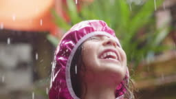 A happy girl is playing in the rain and is happy because she has fun.