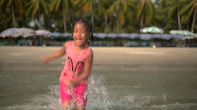 happy girl jumping on the seashore in water at beach - one girl only stock videos & royalty-free footage