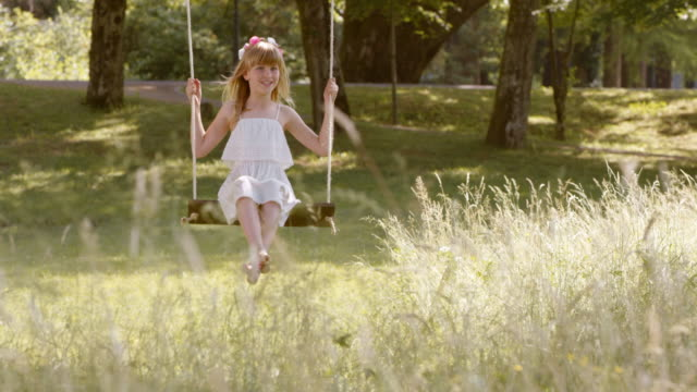 SLO MO DS Happy girl on a swing in nature