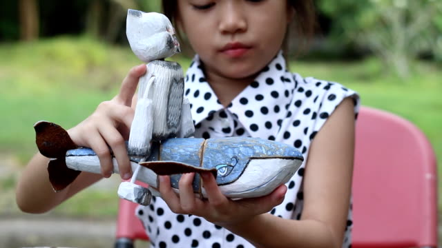 happy girl playing wooden whale puppet - puppet stock videos & royalty-free footage