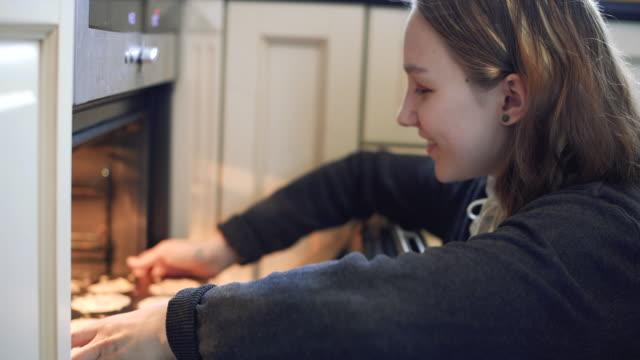 幸せな女の子は台所でオーブンでケーキを入れて - マフィン点の映像素材/bロール