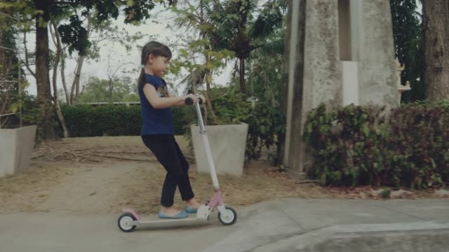happy girl riding a scooter - nur kinder stock-videos und b-roll-filmmaterial