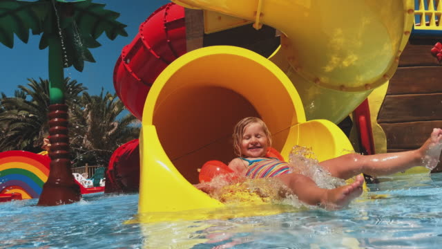 happy girl riding down the yellow water slide - inflatable stock videos & royalty-free footage