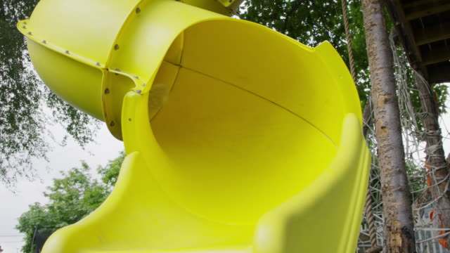 happy girl sliding on yellow slide at playground / provo, utah, united states - provo stock videos & royalty-free footage