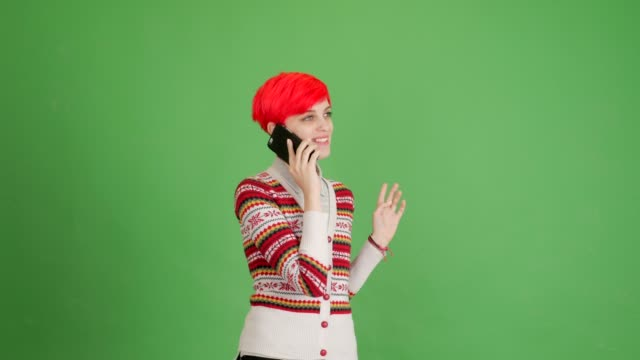 happy girl speaks by smartphone on green background - blouse stock videos & royalty-free footage