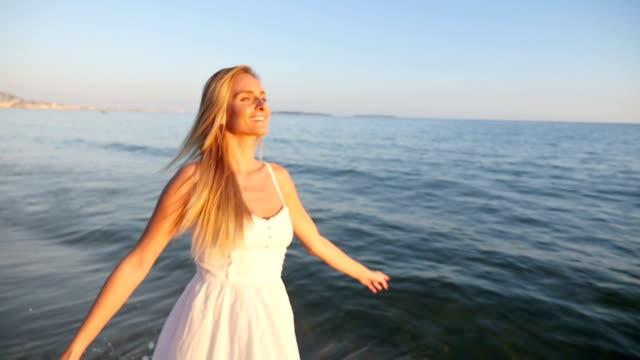 Glad tjej spinning på stranden