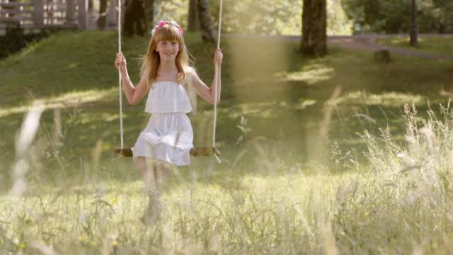 SLO MO gelukkig meisje swingende onder een boom in de natuur